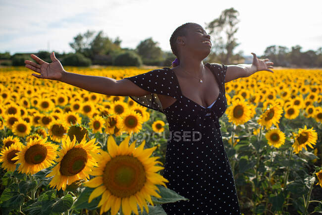 Delighted African American female in dress standing in sunflower field with outstretched arms and enjoying summer with closed eyes — Stock Photo
