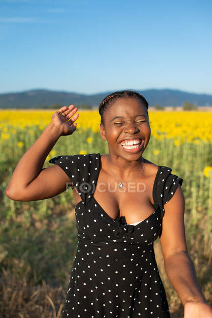 Cheerful African American female in dress standing in blossoming field with sunflowers while laughing with closed eyes and enjoying sunny day in summer — Stock Photo