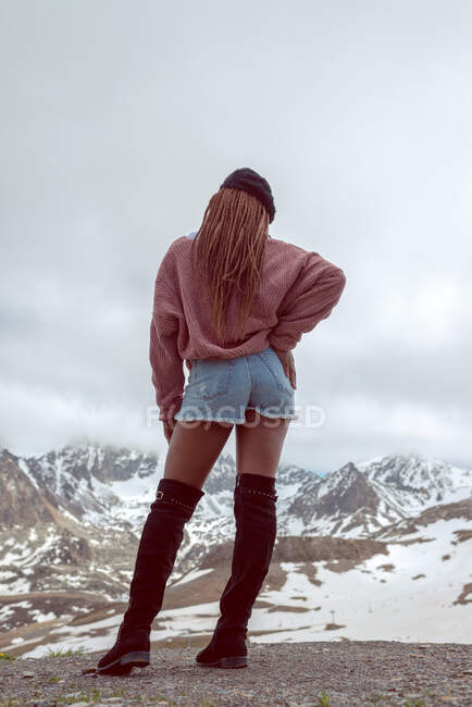 From below back view of unrecognizable African American female in stylish outfit standing on background of snowy mountains in winter — Stock Photo