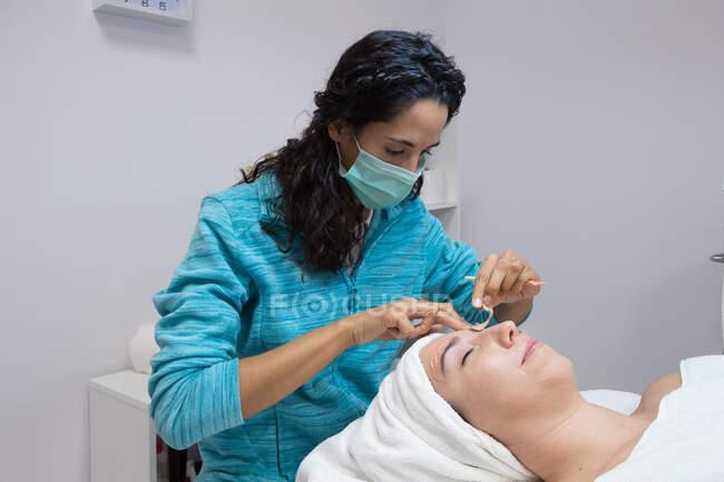 Crop estetista anonimo in maschera trattare donna adulta con gli occhi chiusi durante la procedura facciale nel centro di bellezza — Foto stock