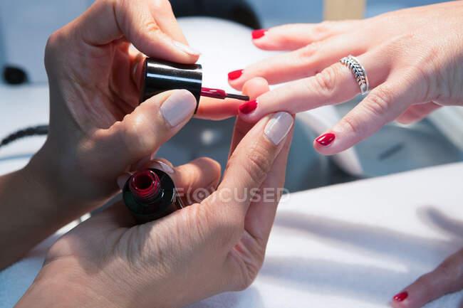 Ritagli il padrone di bellezza femminile irriconoscibile che applica la vernice rossa a unghia di donna durante procedura di manicure in centro termale — Foto stock
