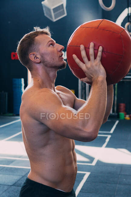Side view of sportsman with naked torso throwing medicine ball during functional workout in gym — Stock Photo