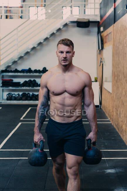 Deportista decidido sin camisa caminando por el gimnasio con pesadas pesas durante el entrenamiento funcional y mirando a la cámara - foto de stock