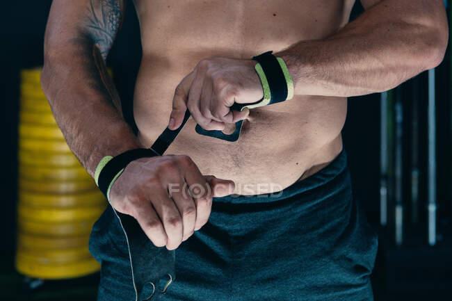 Deportista irreconocible recortado con torso desnudo muscular de pie en el gimnasio y envolviendo muñecas con vendajes mientras se prepara para el entrenamiento funcional - foto de stock