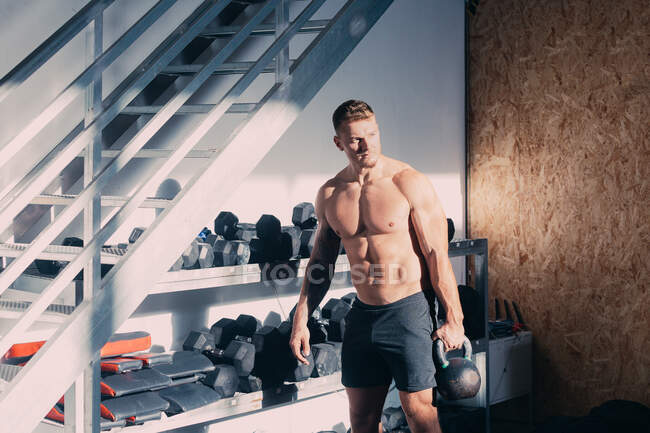 Strong shirtless male with muscular torso carrying heavy kettlebell while standing near stand with sports equipment and preparing for weightlifting exercise during functional training in gym — Stock Photo