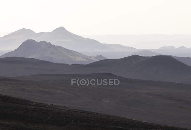 Picturesque scenery of rough mountain range with peaks in dense fog under gloomy sky in highlands — Stock Photo