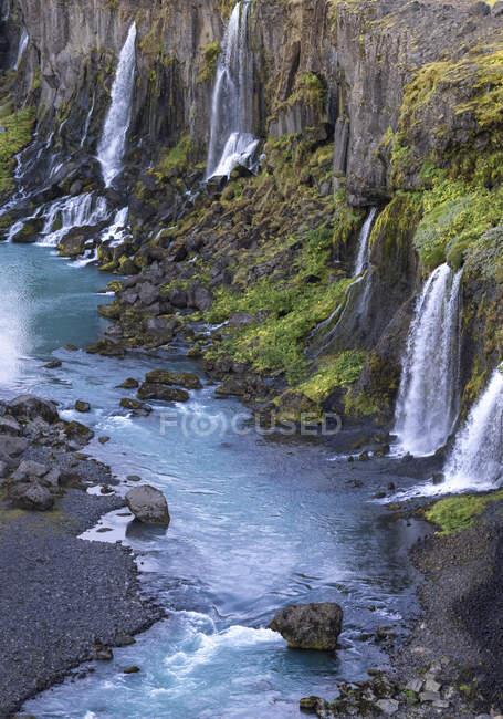 Espectacular vista de las rápidas cascadas que fluyen desde el áspero acantilado rocoso cubierto de exuberante vegetación hacia el tranquilo embalse azul en naturaleza pacífica - foto de stock