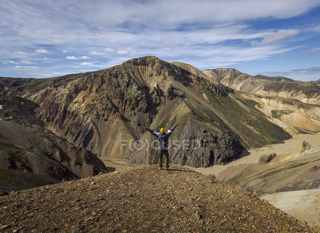 Back view full length male hiker in casual outfit with arms outstretched in excitement standing on dry hilltop against picturesque mountainous terrain on sunny day — Stock Photo