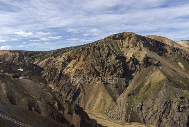 Spectacular landscape of endless rough rocky terrain with dry slopes and random vegetation located under clear blue sky in Iceland — Stock Photo