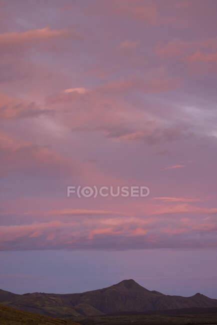 Дивовижний краєвид скелястого гірського пасма з вершинами під величним рожевим небом у сутінках. — стокове фото