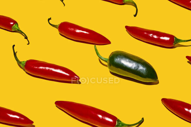 From above of fresh ripe chili peppers with hot green vegetable of different kind on yellow background — Stock Photo