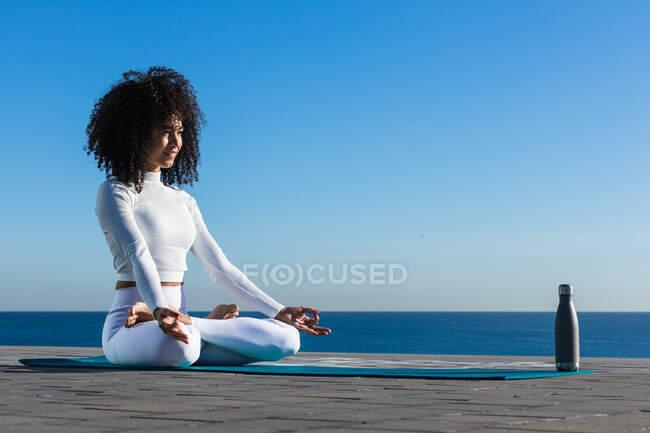 Вид сбоку счастливой босиком женщины с вьющимися волосами, снимающими стресс в положении детской йоги с поднятыми за спиной руками — стоковое фото
