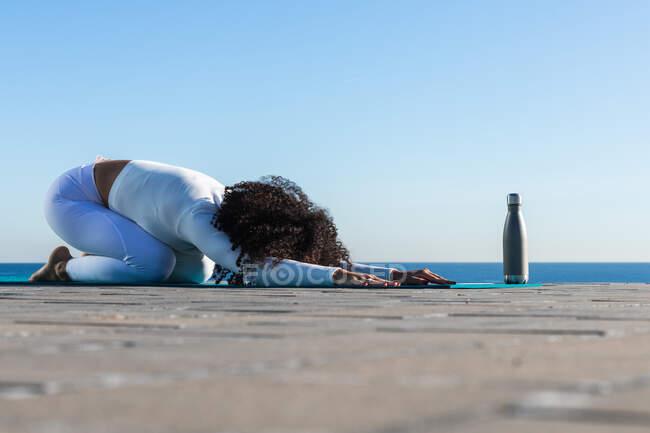 Вид сбоку всего тела босых женщин снимающих стресс в положении детской йоги — стоковое фото