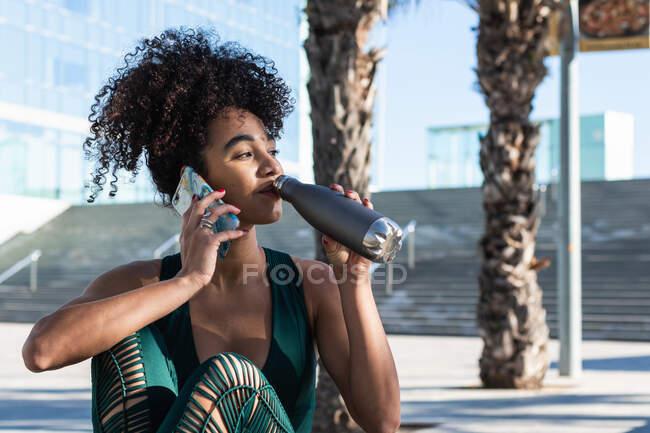 Athlète brésilienne positive portant des vêtements de sport ayant une conversation sur son téléphone portable tout en buvant de l'eau provenant d'une bouteille réutilisable pendant la pause d'entraînement — Photo de stock