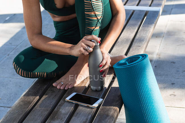 High angle of crop faceless ethnic female athlete sitting on bench with smartphone and sports mat while opening eco friendly water bottle — Stock Photo