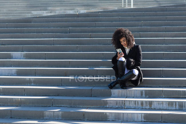 Elegante donna brasiliana sorridente che indossa vestiti caldi seduti sulle scale e naviga sul cellulare mentre guarda altrove — Foto stock