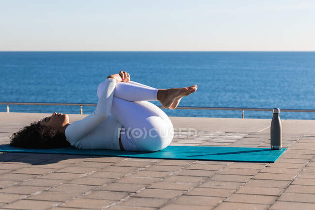 Full body side view of tranquil female lying on sports mat in Wind Removing asana during meditation on embankment — Stock Photo