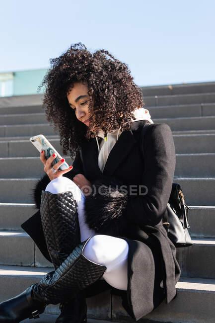 Fro ci-dessous élégant sourire brésilien femme portant des vêtements chauds assis sur les escaliers et surfer téléphone mobile tout en regardant loin — Photo de stock