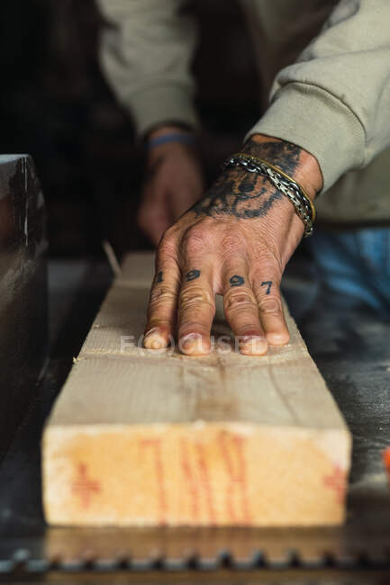 Unrecognizable crop male woodworker without a thumb processing piece of wood at workbench while working in joinery — Stock Photo