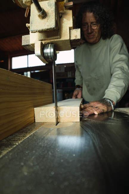 Von unten männlicher Schreiner mittleren Alters ohne daumenschneidendes Stück Holz mit Bandsäge bei der Arbeit in der Tischlerei — Stockfoto