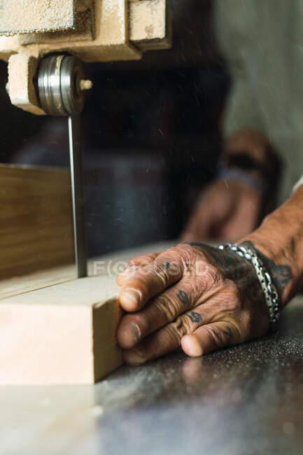 Männlicher Tischler ohne Daumen beim Holzschneiden mit Bandsäge bei Schreinerarbeiten unkenntlich gemacht — Stockfoto