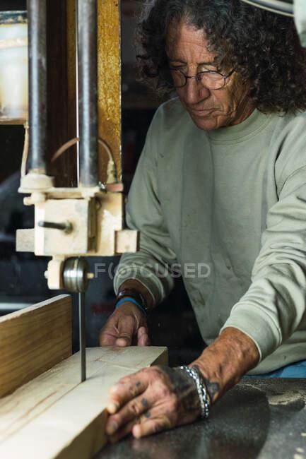 Männlicher Schreiner mittleren Alters schneidet während seiner Arbeit in der Tischlerei mit der Bandsäge ein Stück Holz — Stockfoto