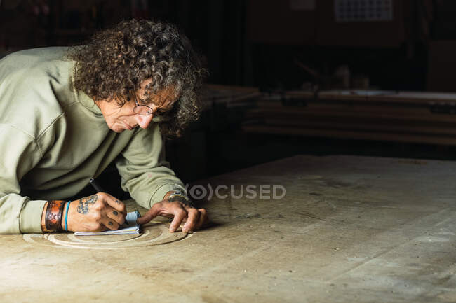Focused mature male joiner drawing sketch in notepad while working at table in woodworking workshop — Stock Photo