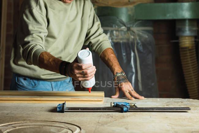 Männlicher Tischler beim Arbeiten am Tisch in Tischlerei nicht wiederzuerkennen, indem er Leim auf Holzstück aufträgt — Stockfoto