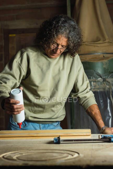Konzentrierter, reifer Tischler, der während der Arbeit am Tisch in der Tischlerei Leim auf ein Stück Holz aufträgt — Stockfoto