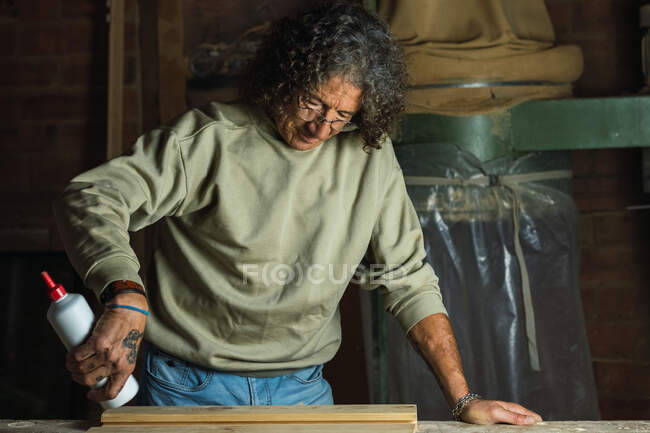 Focused mature male carpenter applying glue on piece of wood while working at table in joinery workshop — Stock Photo