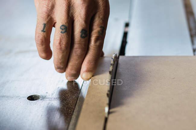 Nahaufnahme der Ernte unkenntlich männliche Schreiner beim Holzschneiden mit Kreissäge in Tischlerei — Stockfoto
