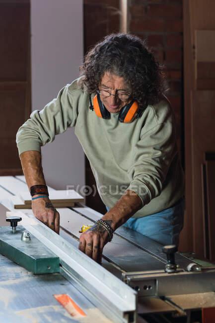 Menuisier masculin concentré dans des écouteurs de protection coupant la planche en bois avec la scie circulaire dans l'atelier poussiéreux — Photo de stock
