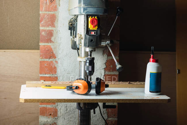 Contemporary drilling machine and protective headphones placed in woodworking workshop with shabby walls — Stock Photo