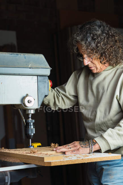 Focused mature male carpenter without a thumb drilling hole in wooden plank while working in dusty carpentry workshop — Stock Photo