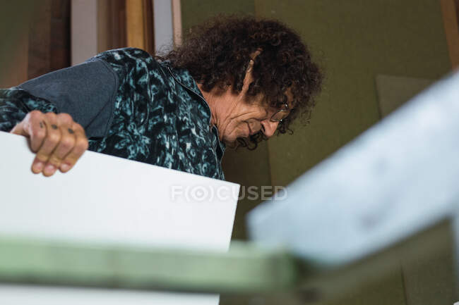 Side view low angle of mature male joiner working with piece of plywood in carpentry workshop — Stock Photo