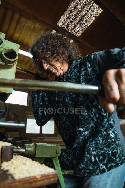 From below focused mature male tattooed carpenter holding handle of woodworking machine while working in professional joinery — Stock Photo