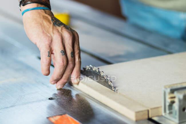 Nahaufnahme der Ernte unkenntlich männlichen Tischler ohne Daumen Schneideholz mit Kreissäge in Tischlerei — Stockfoto