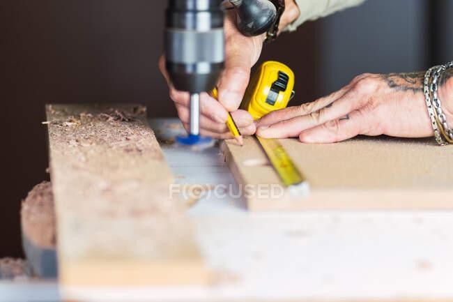Schnappen gesichtslosen tätowierten männlichen Meister ohne Daumen messen Stück Holzplanke und Markierungen mit Bleistift beim Erstellen neuer Objekt in der Werkstatt — Stockfoto
