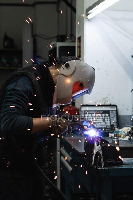 Вид сбоку на неузнаваемого ремонтника в защитном шлеме с помощью горелки при сварке металлических деталей во время работы в гараже — стоковое фото
