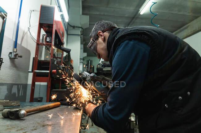 Vista lateral do mecânico masculino adulto em roupas casuais e óculos de soldagem polimento de detalhes de metal com ferramenta de moagem na bancada na garagem — Fotografia de Stock