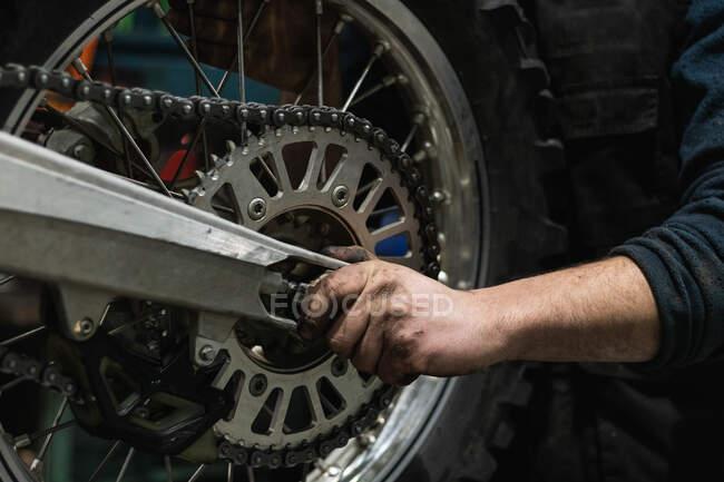 Бічний вид урожаю анонімного ремонтника в жилеті встановлення мотоциклетного ланцюга під час роботи в сучасному гаражі — стокове фото