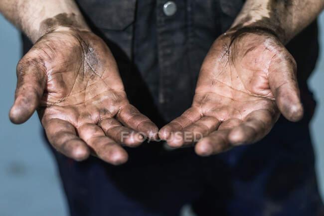 Anonymer Mechaniker zeigt schmutzige Hände in Autowerkstatt — Stockfoto