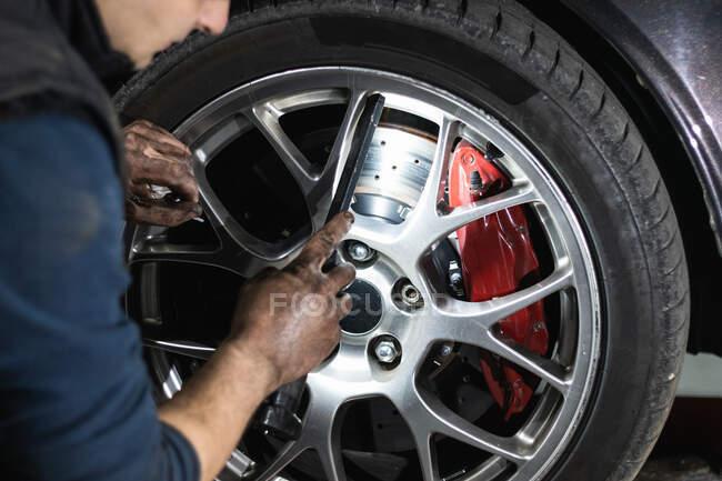 Анонімний чоловічий механік перевіряє стан автомобільного колеса під час ремонту автомобіля в гаражі. — стокове фото