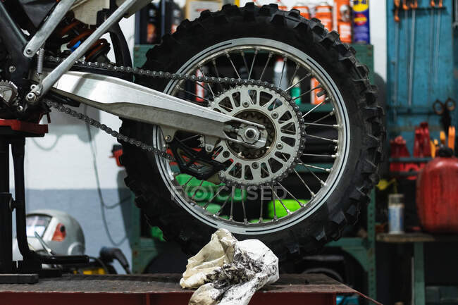Wheel of vintage motorcycle with chrome details and chain placed on platform lift during maintenance in garage — Stock Photo