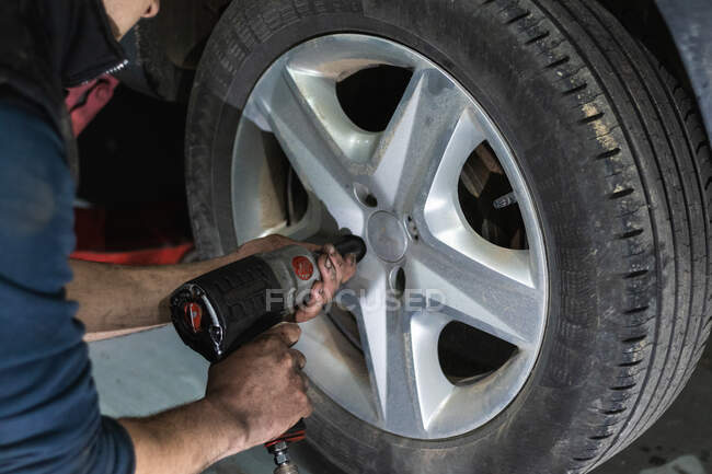 Crop anonymous male mechanic using automatic screwdriver while changing wheels during car maintenance in garage — Stock Photo