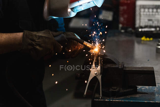 Side view of unrecognizable repairman in protective helmet using torch while welding metal details during work in garage — Stock Photo
