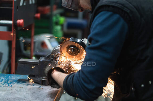 Seitenansicht eines erwachsenen Mechanikers in Freizeitkleidung und Schutzbrille und Handschuhen, der Metalldetails mit einem kantigen Schleifwerkzeug während der Arbeit in der Garage schneidet — Stockfoto