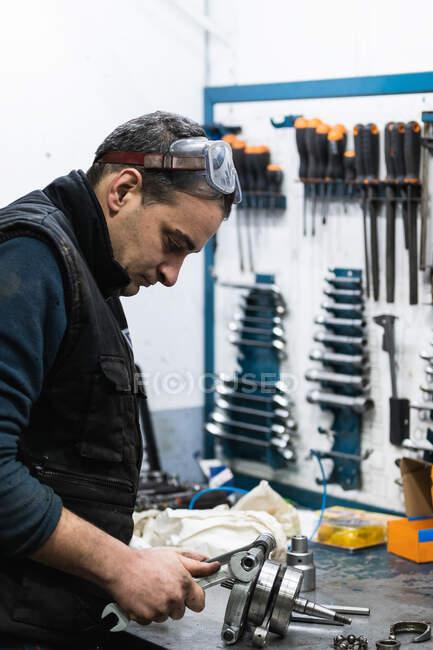 Бічний вид сконцентрованого дорослого чоловіка - автомеханіка в захисних окулярах і рукавичках збирає колінчастий вал під час роботи в гаражі. — стокове фото