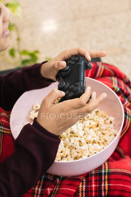 Crop ethnic boy in casual wear playing video game with joypad while sitting on cozy sofa with popcorn and covering legs with plaid — Stock Photo