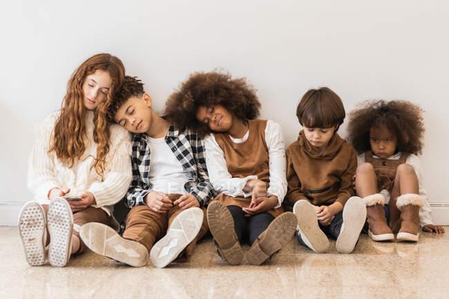 Gruppe von entzückenden lustigen multirassischen Kindern in stylischer Kleidung, die sich auf dem Boden in der Reihenfolge der Körpergröße ausruhen — Stockfoto